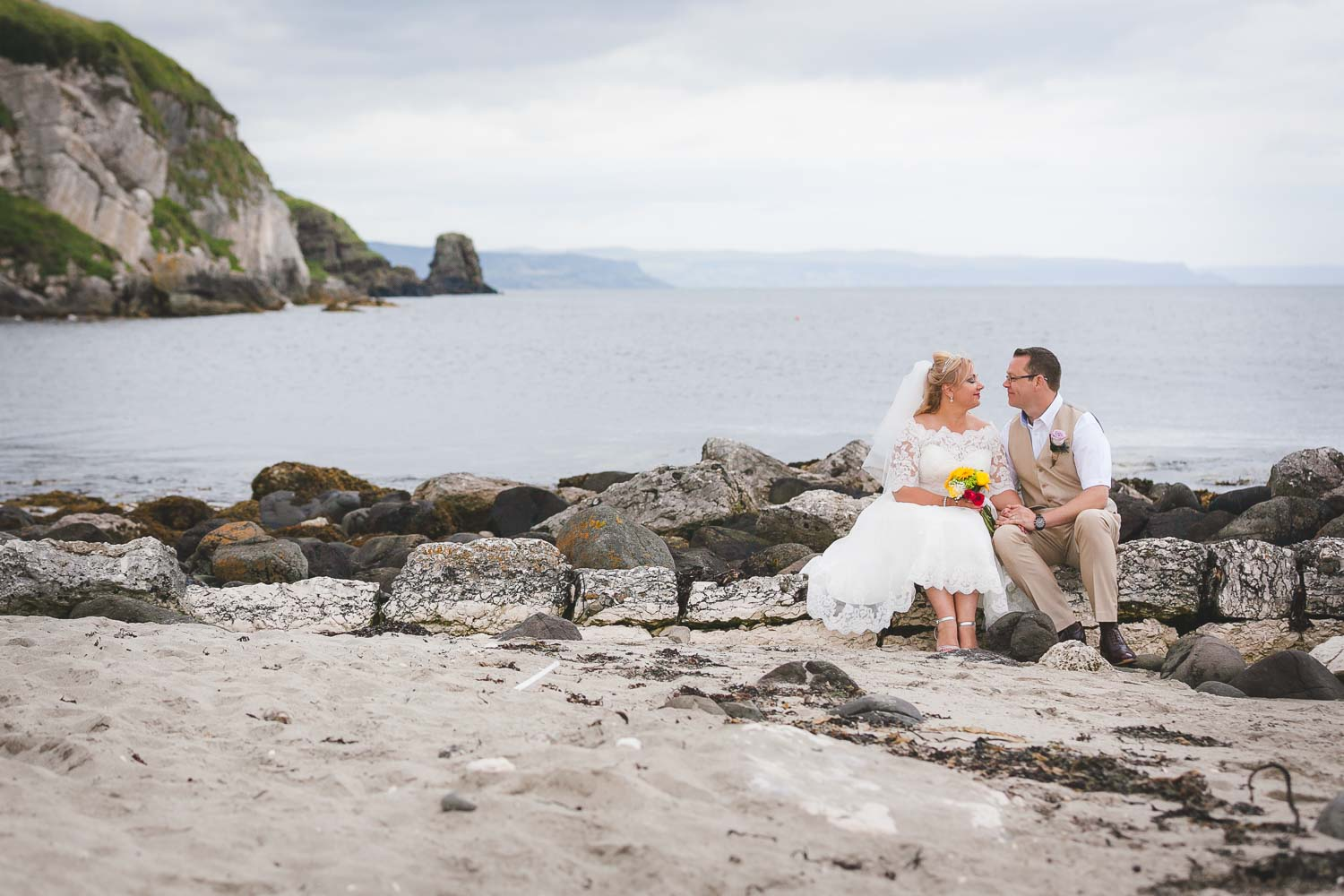 Bride and groom sitting on rocks at beach