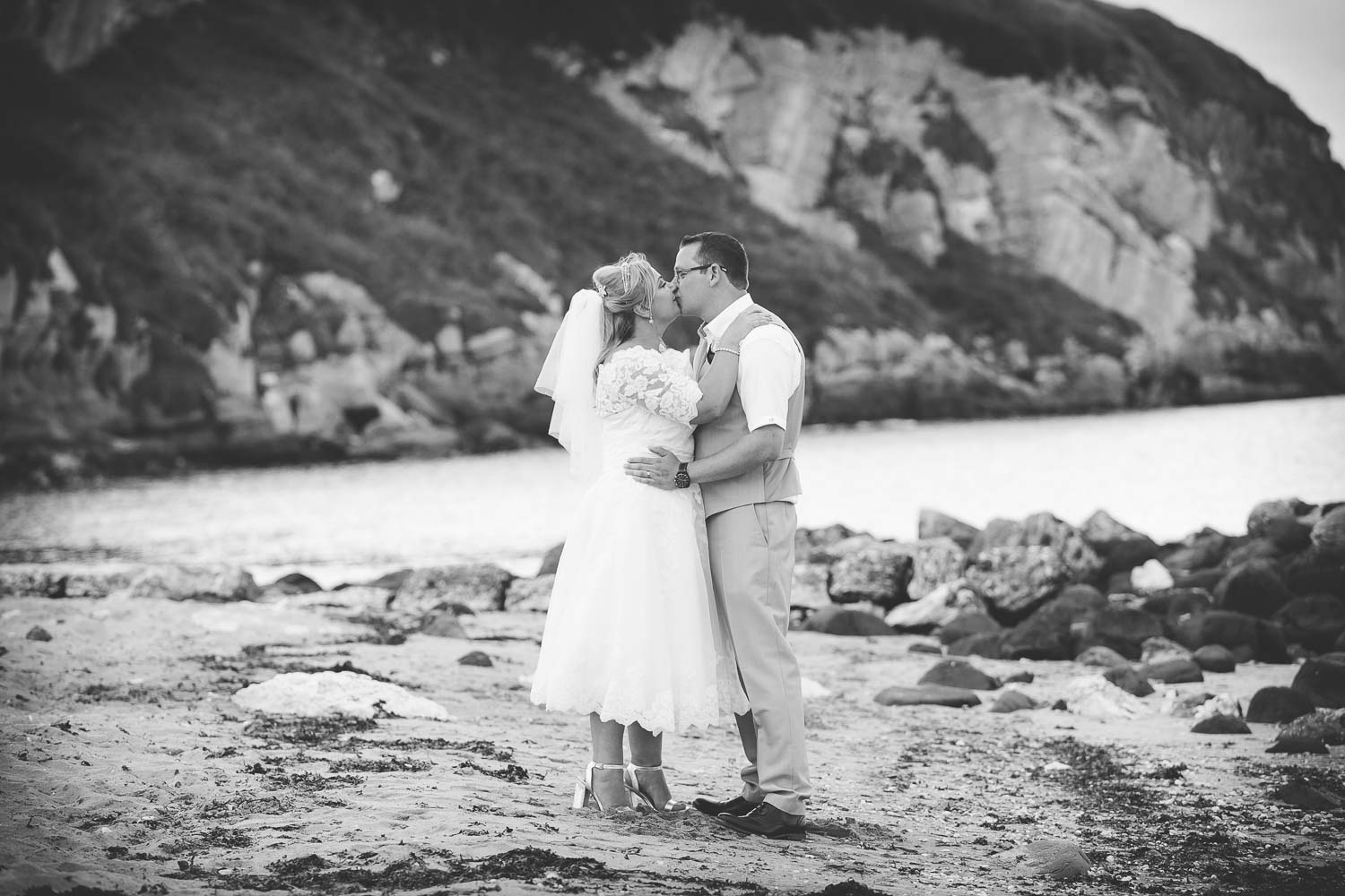 Bride and Groom on beach kissing black and white