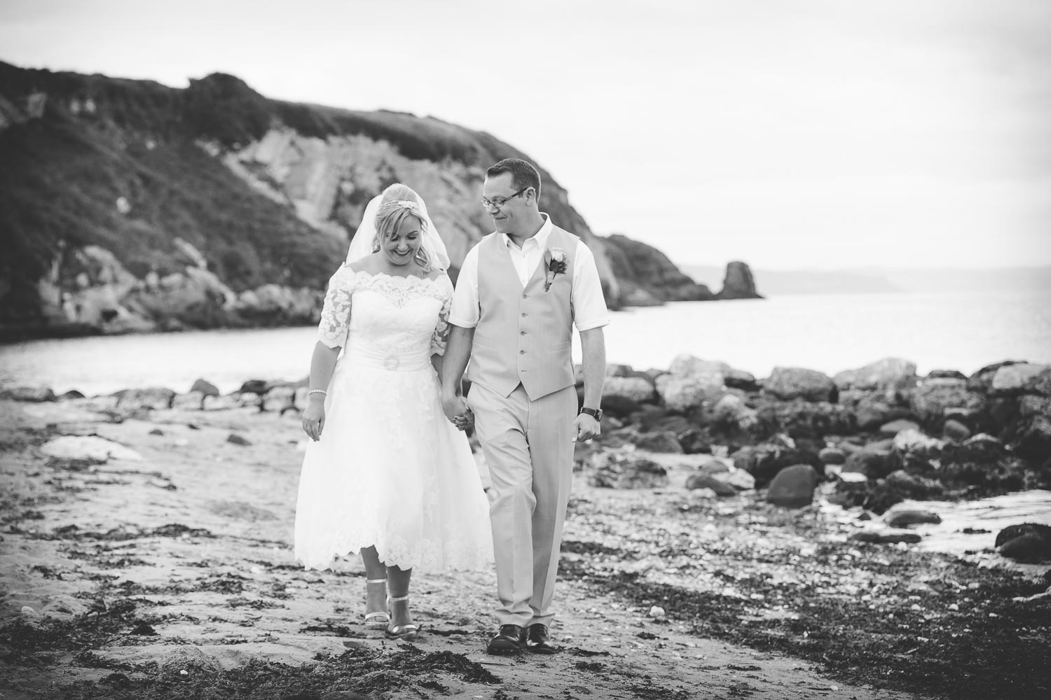 Bride and Groom walking on beach black and white