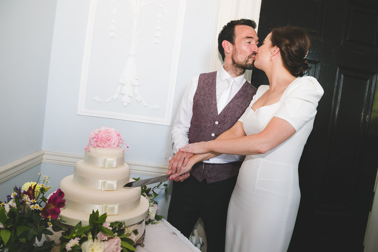 Bride and Groom cutting cake kissing