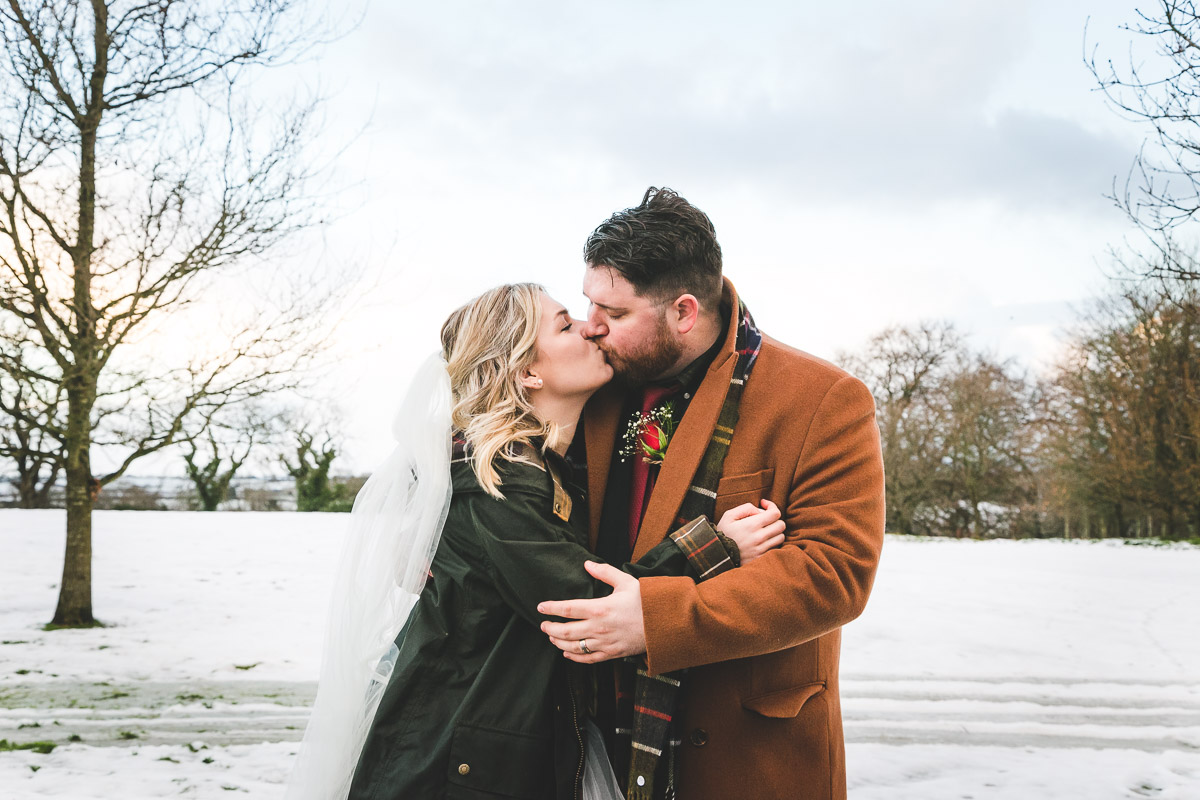 Wedding couple embrace in snow